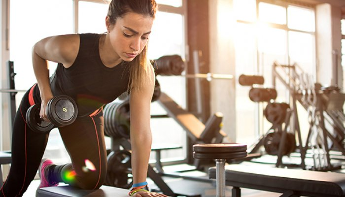 Fitness girl lifting dumbbell in the morning